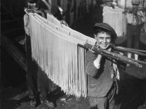 Boys carrying spaghetti in a macaroni factory in Naples, Italy. 1929